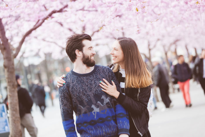 Young hipster couple embracing and smiling in Stockholm with cherry blossoms at Kungstradgarden, the swedish for Kings Garden. Love and friendship concepts with a hipster theme.